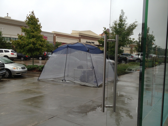 iPhone 5 customer in tent - Apple Store The Promenade at Chenal, Little Rock, Arkansas